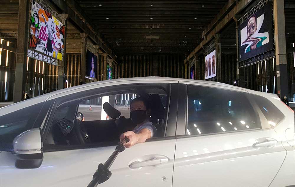 Ricardo Shimosakai dentro de seu carro Honda Fit branco, no interior do galpão da exposição, estica o braço com um pau de selfie para tirar foto. Ao fundo, os painéis com as obras ao alto.