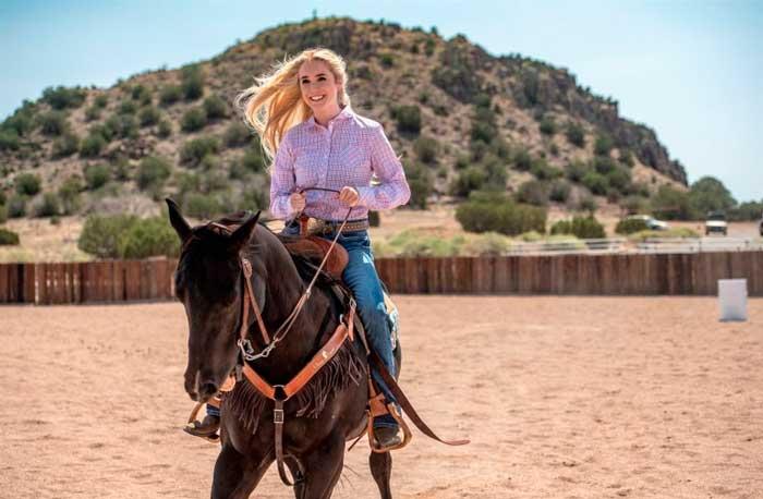 Uma garota sentada em um cavalo, corre pela área cercada de um haras. Ele tem cabelos loiros, usa camisa rosa, calça jeans e o cavalo tem pelos marrom escuro. Ao fundo há uma montanha com arbustos.