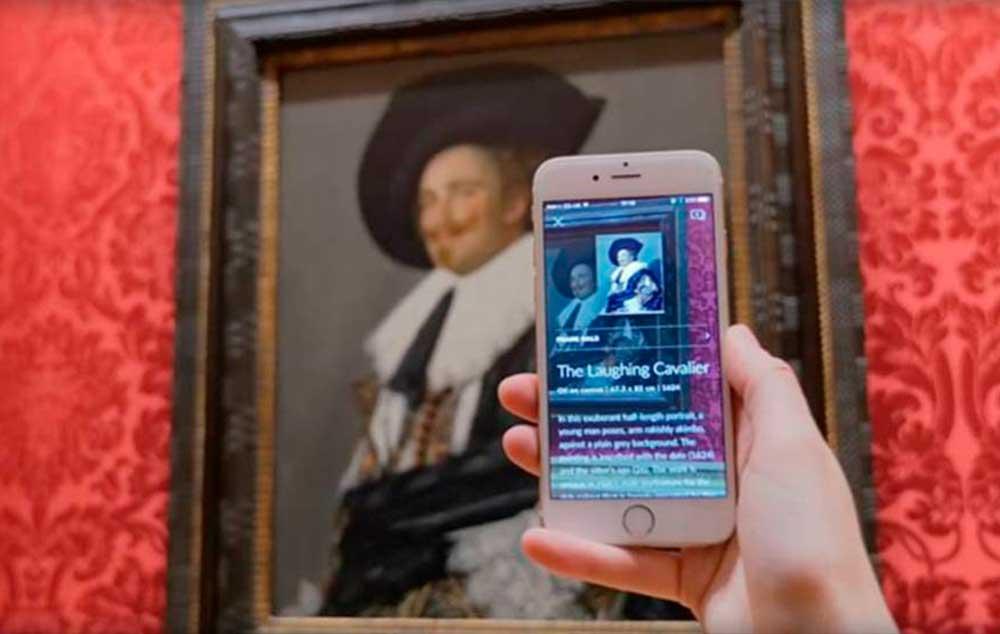 Uma mão de uma pessoa segurando um celular branco na frente de uma obra de arte. Na tela do celular aparecem informações da obra. Ao fundo o quadro em uma parede vermelha.