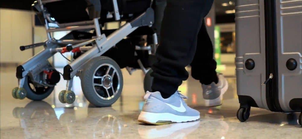 imagem da parte inferior de uma cadeira motorizada, as pernas de um acompanhante e uma mala, andando pelo aeroporto