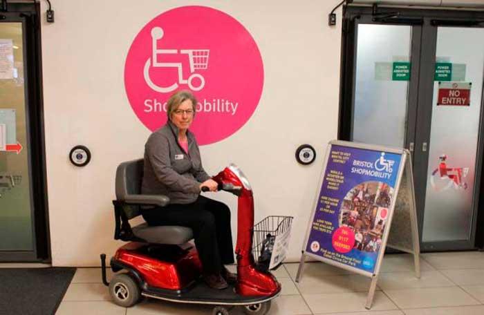 """mulher sentada em uma scooter, atrás de um painel escrito """"Shopmobility"""""""
