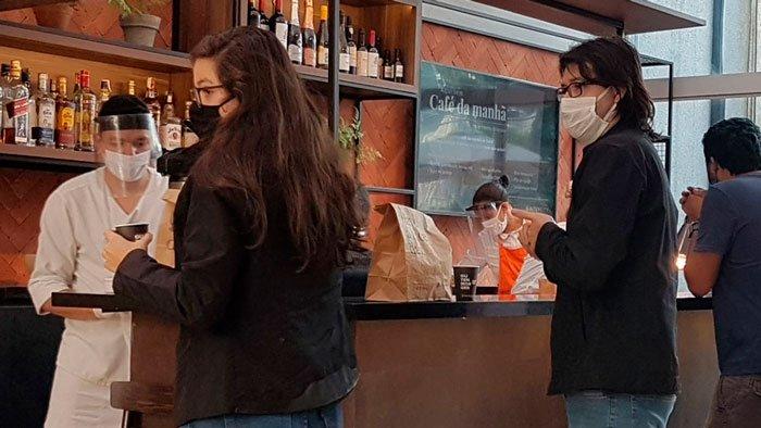 Foto de pessoas em uma fila para pegar sacolas com café da manhã. Estão em um balcão de atendimento do restaurante. Todas estão usando máscara ou face shield.