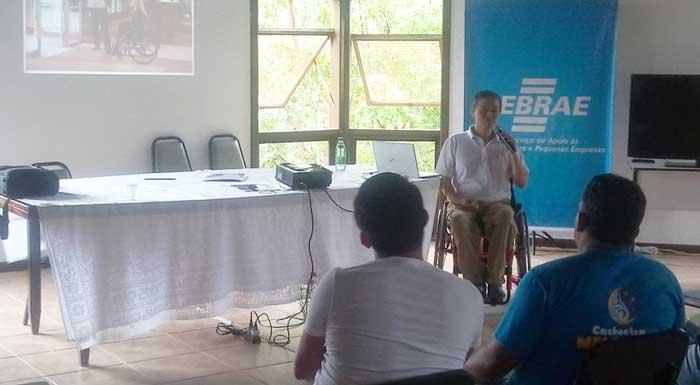 Ricardo Shimosakai está sentado em sua cadeira de rodas, segurando um microfone. Ao seu lado, uma mesa com um projetor, e atrás um telão. À sua frente, platéia assistindo à sua palestra.