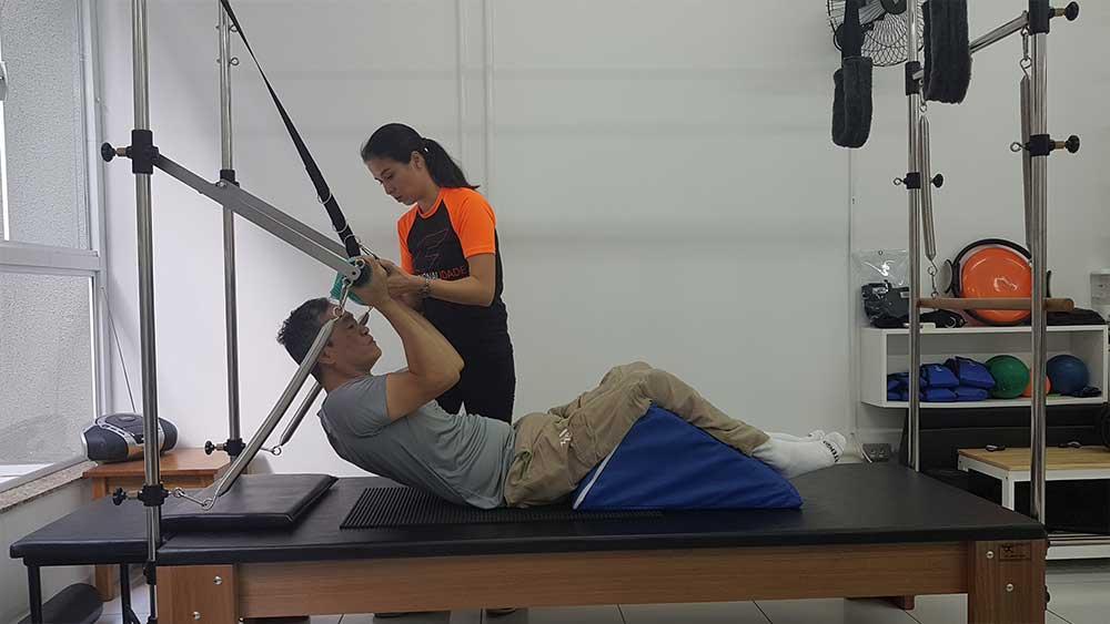 Ricardo Shimosakai está deitado de costas em um aparelho de pilates, pernas apoiadas em uma almofada triangular, segurando uma barra tensionada por molas. Sabrina Kyoko de Paula está de pé ao seu lado, passando orientações.